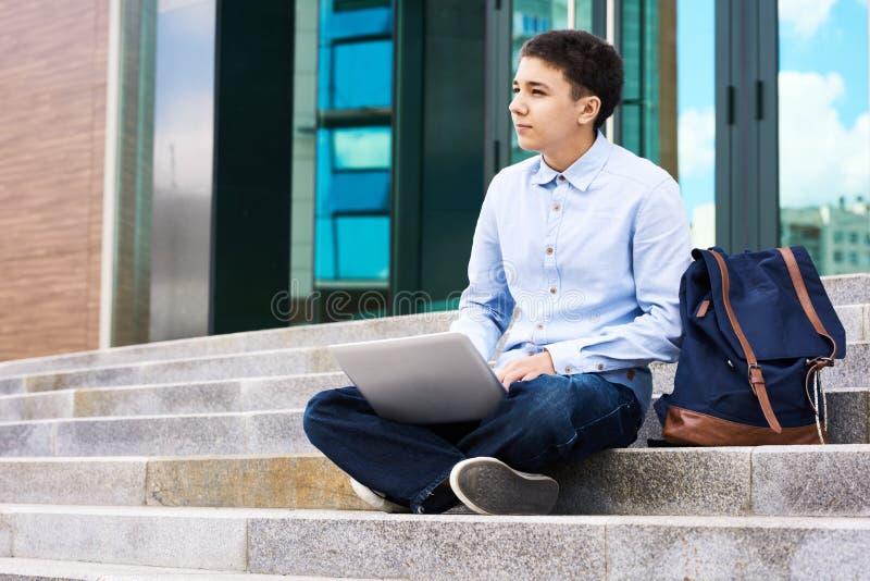 Peinzende Schooljongen met Laptop in openlucht royalty-vrije stock afbeeldingen