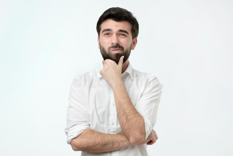 Peinzende Spaanse mens in wit overhemd tegen een witte achtergrond stock fotografie