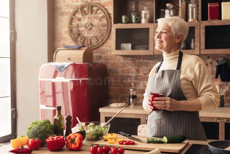 Peinzende teruggetrokken dame die van koffiepauze genieten bij keuken royalty-vrije stock afbeelding