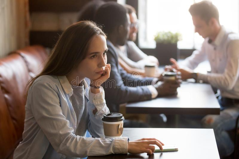 Peinzende verstoorde jonge meisjeszitting alleen bij lijst in koffie royalty-vrije stock foto