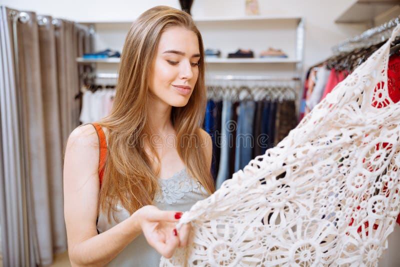 Peinzende vrouw die en kleding in winkel denken kiezen stock afbeeldingen