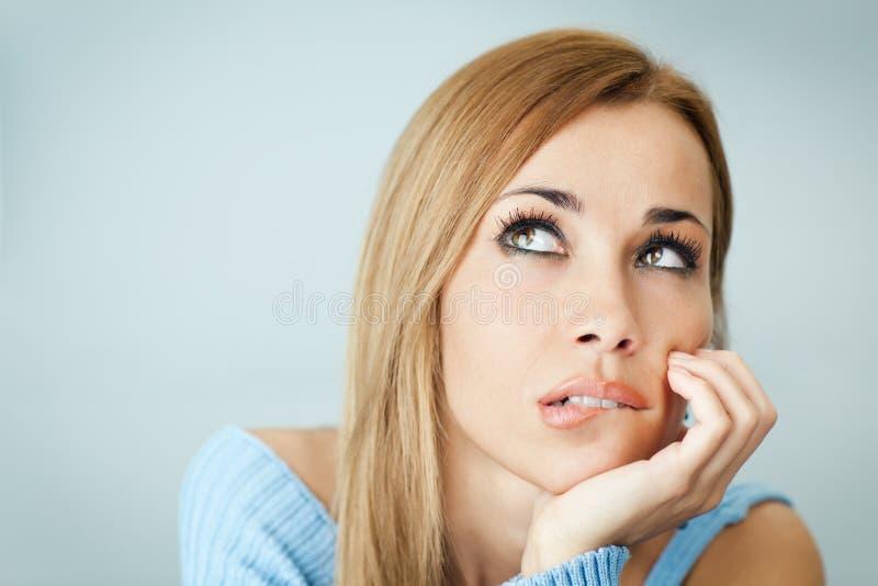 Peinzende vrouw het bijten lippen stock fotografie