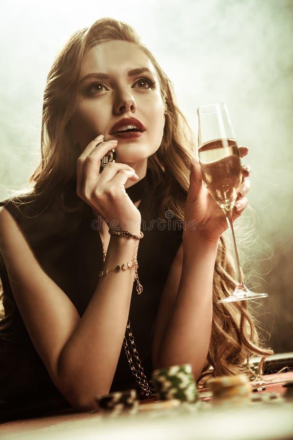 Peinzende vrouw met drank en oiker spaander het spelen pook stock fotografie