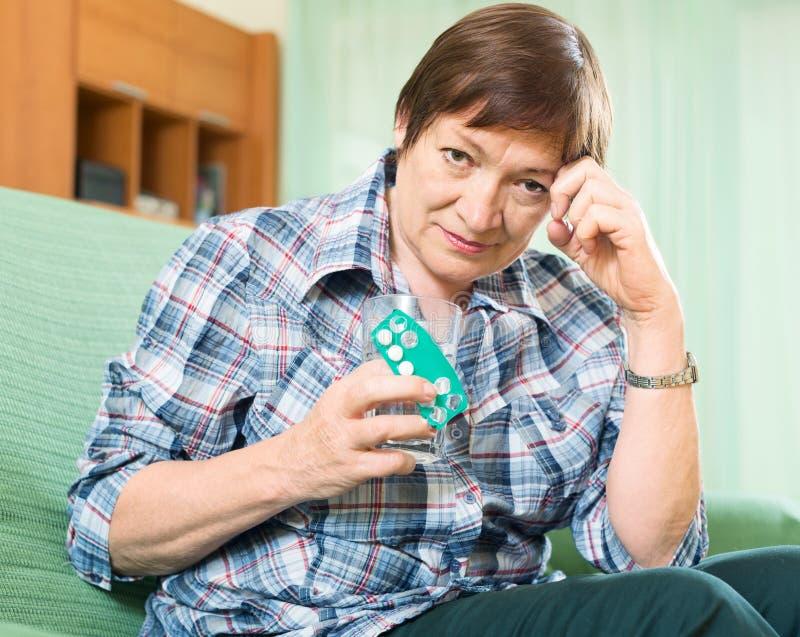 Peinzende vrouwelijke gepensioneerde met pillen en glas water stock foto