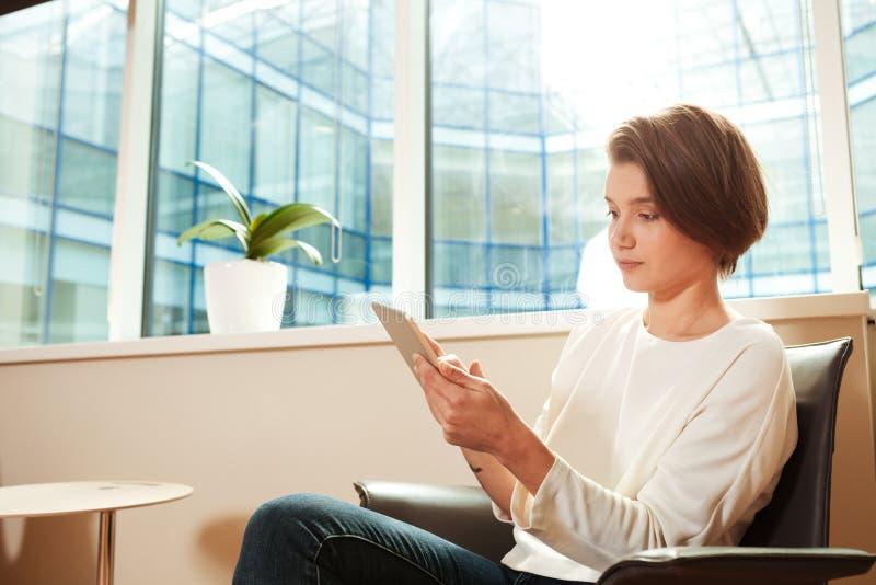 Peinzende vrouwenzitting in bureau en het gebruiken van tablet royalty-vrije stock foto's