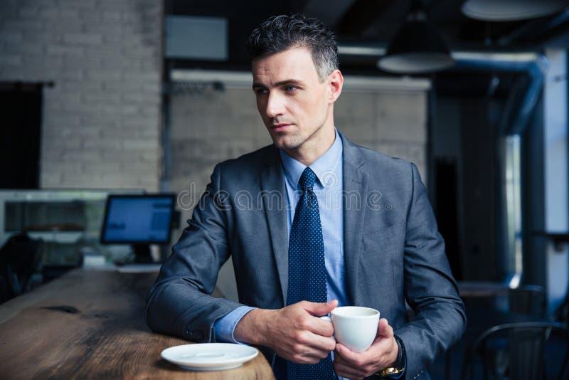 Peinzende zakenman het drinken koffie in koffie stock afbeelding