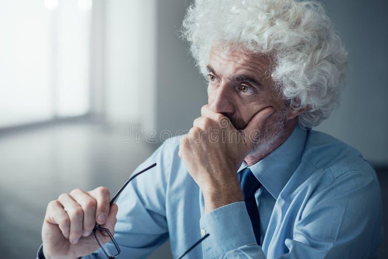 Peinzende zakenman met hand op kin stock afbeelding