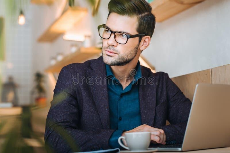 Peinzende zakenman met laptop in koffie stock foto