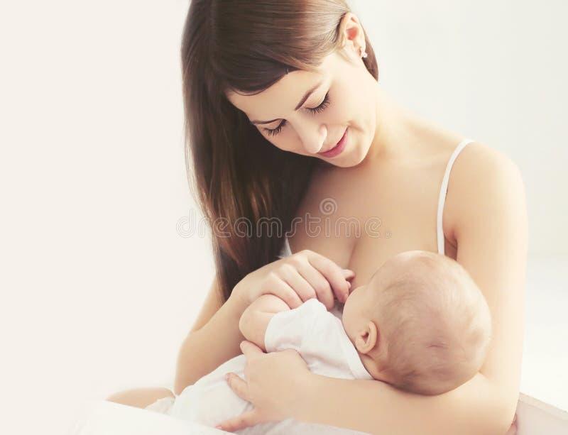 Peito de alimentação da mãe nova macia da foto seu bebê em casa fotografia de stock royalty free
