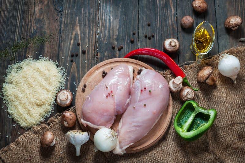 Peito de Chiken em uma placa de corte com frutas e legumes diferentes das ervas na opinião superior do fundo de madeira rústico fotografia de stock