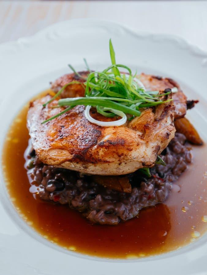 Peito picante grelhado da galinha com risoto marrom no caldo imagens de stock