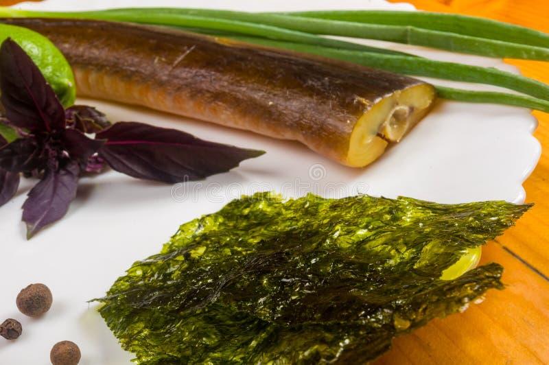 Peixe-agulha fumado com cal, manjeric?o, cebolas verdes, piment?o, microplaquetas do nori, especiarias, azeite em um prato cer?mi imagens de stock royalty free