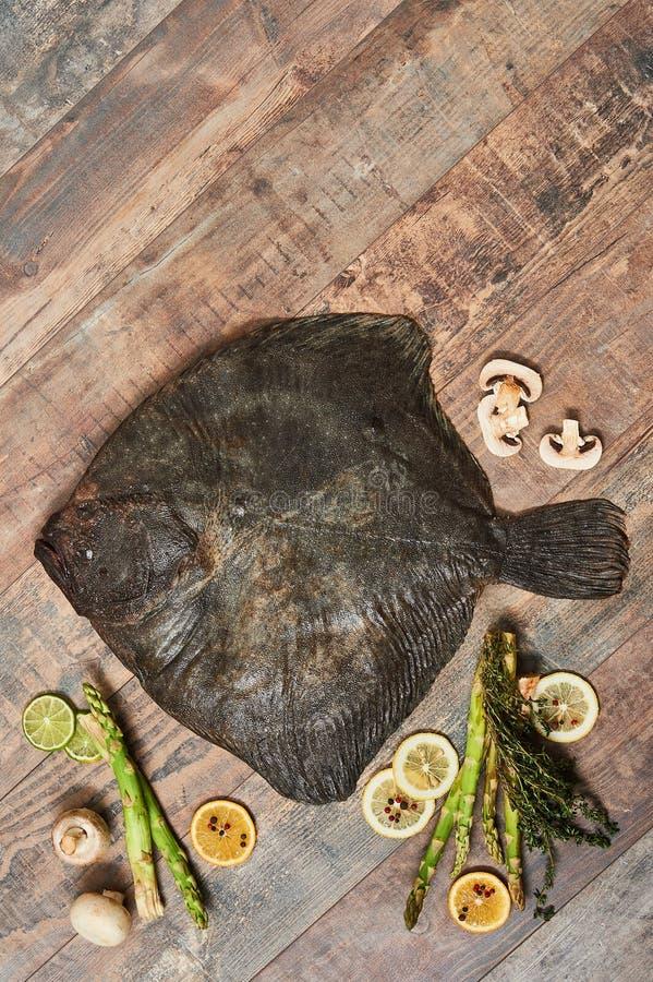 Peixe heterossomo cru cru na tabela de madeira fotografia de stock royalty free