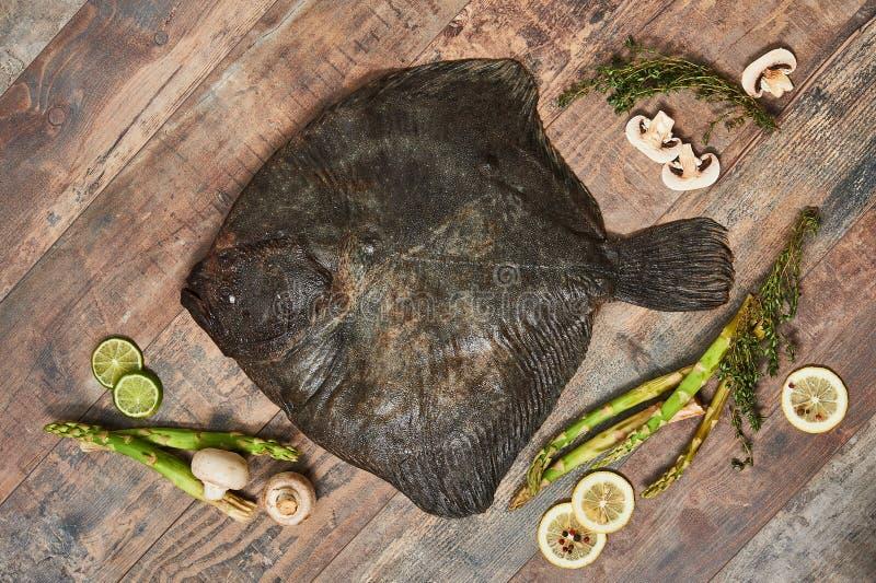 Peixe heterossomo cru cru na tabela de madeira fotografia de stock