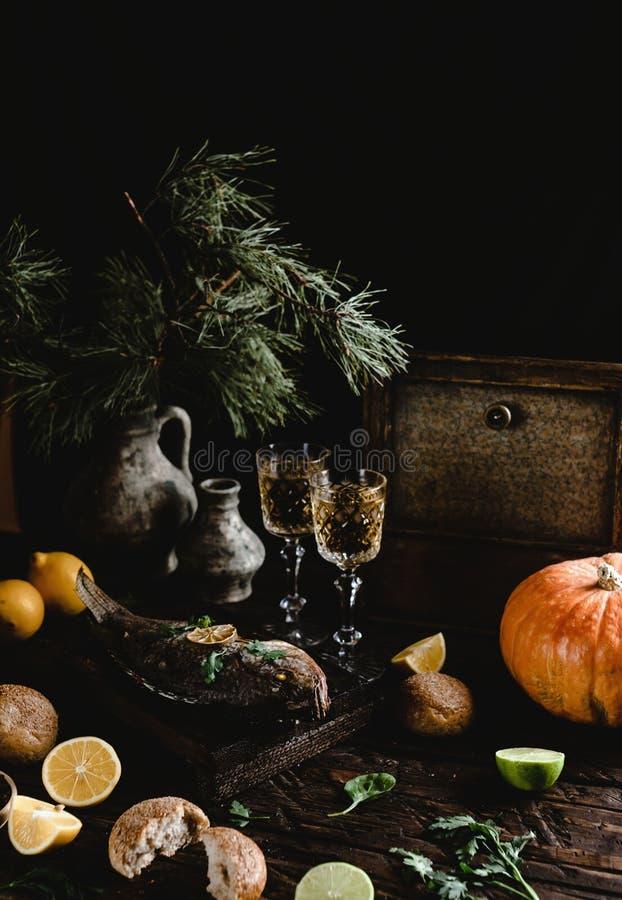 Peixes cozidos com limão e ervas na placa de madeira com vidros de vinho branco foto de stock royalty free