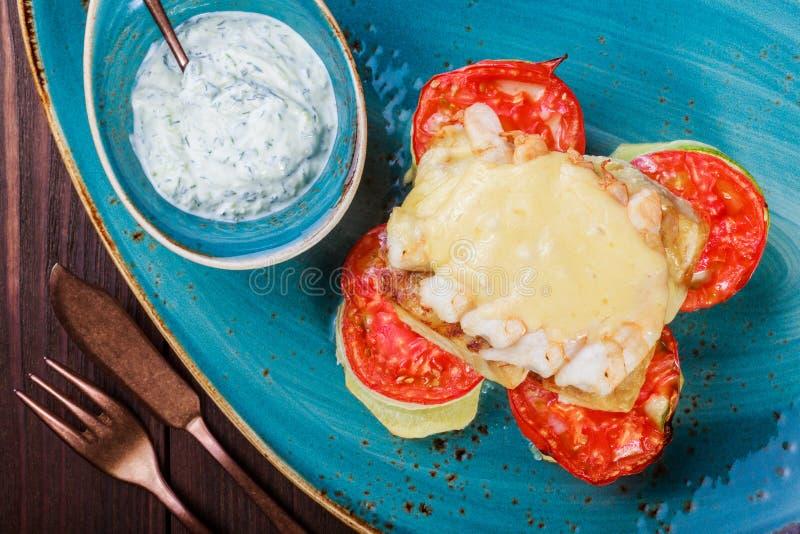 Peixes cozidos dos salmões com camarão, queijo, tomates, beringela e molho no fundo de madeira fotografia de stock