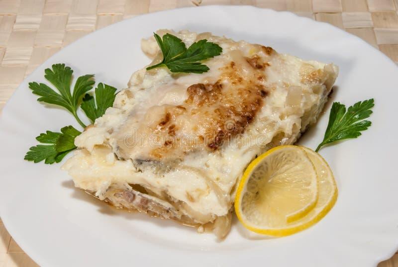 Peixes cozidos sob o queijo foto de stock
