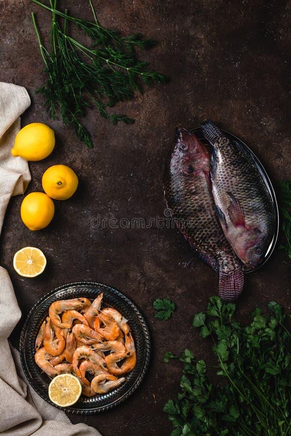 Peixes crus, camarão, ervas com limões e toalha de mesa no tampo da mesa escuro imagens de stock