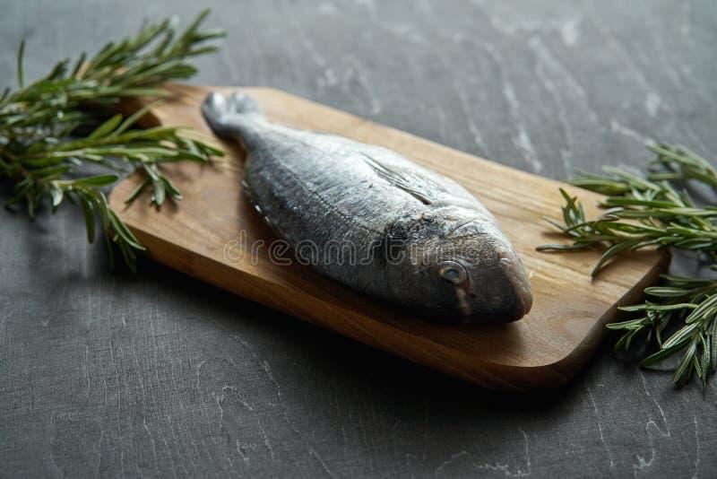 Peixes crus frescos do dorada com alecrins, pimenta e sal em uma placa de madeira e em uma tabela preta imagens de stock