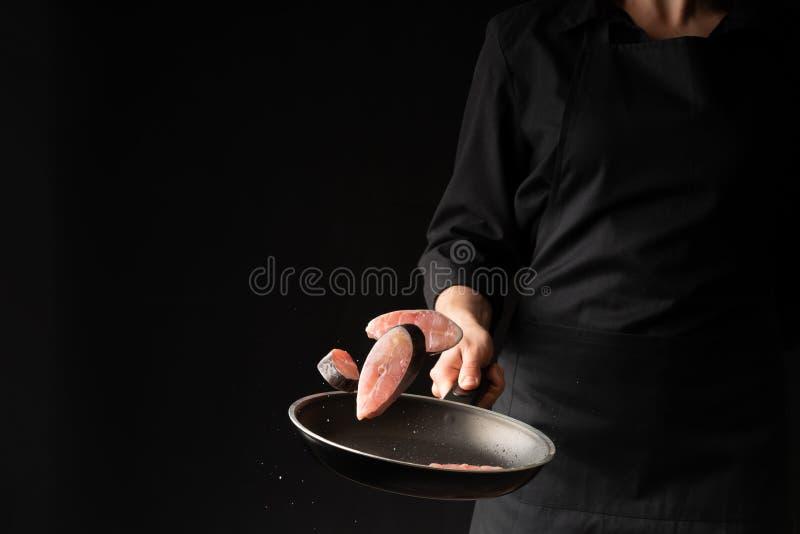 Peixes da fritada do cozinheiro do cozinheiro chefe em uma chapa para assar em um fundo preto Foto horizontal Alimento de mar Ali foto de stock royalty free