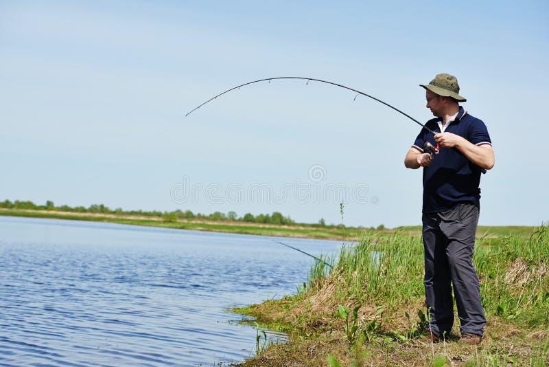 Peixes da pesca de Fisher com haste foto de stock