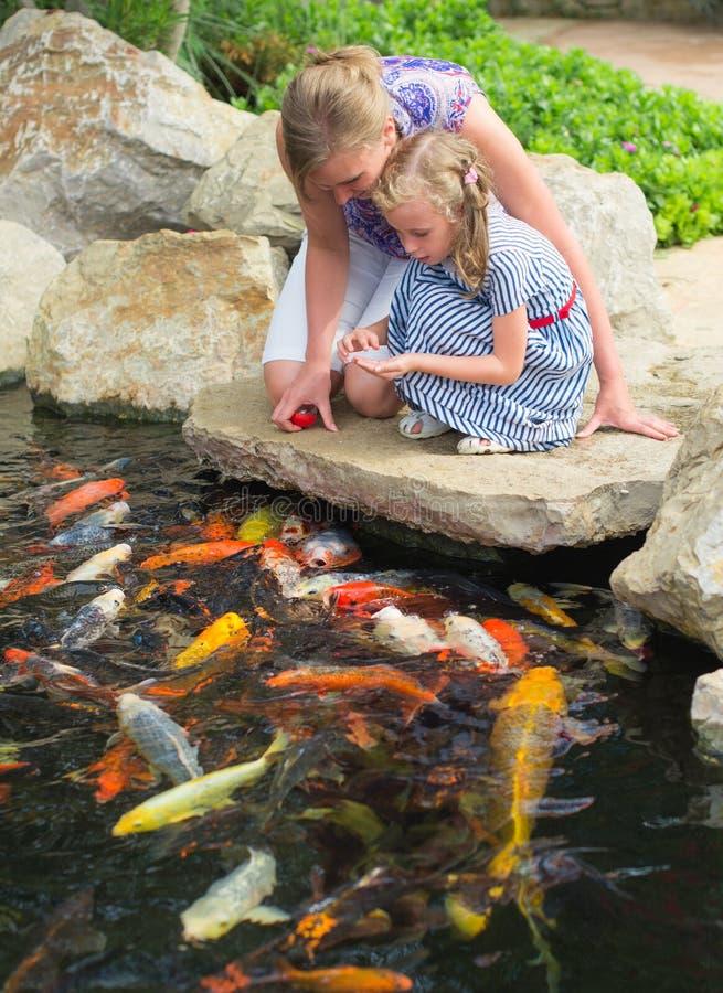 Peixes de alimentação da mulher e da filha imagem de stock