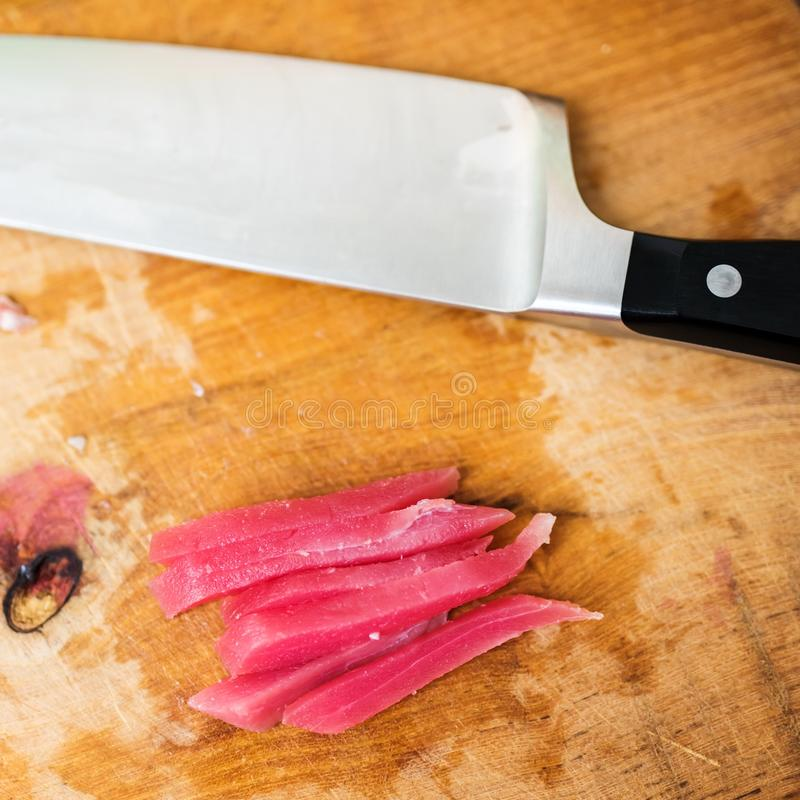Peixes de atum do corte em partes minúsculas imagens de stock