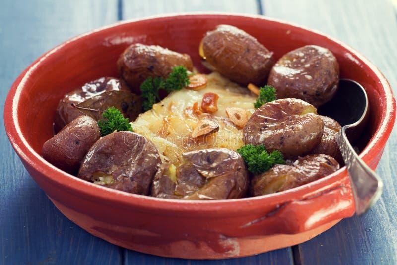 Peixes de bacalhau com a batata no prato cerâmico imagens de stock