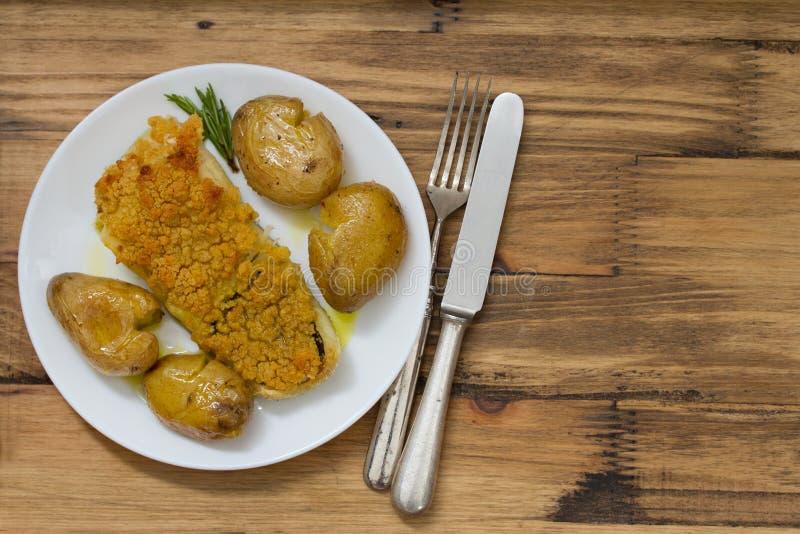 Peixes de bacalhau fritados com broa e batata no prato fotos de stock