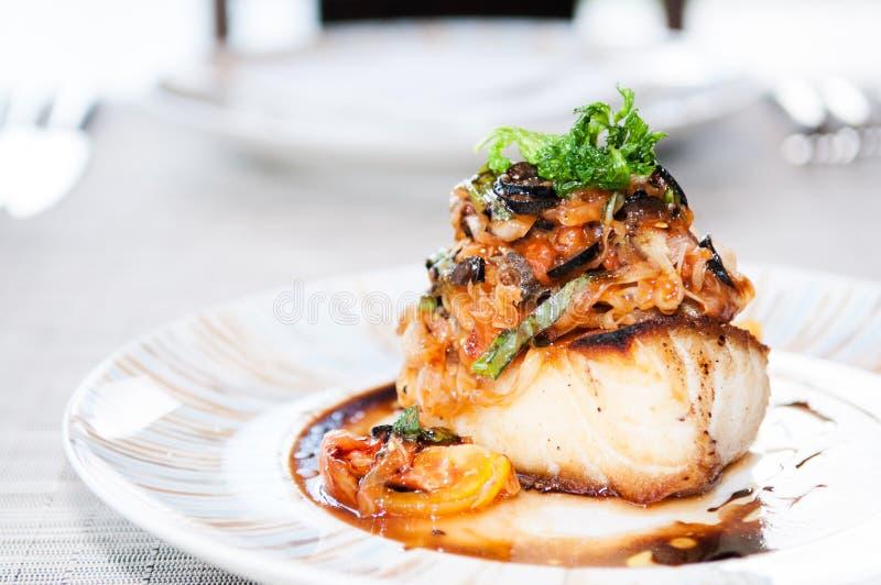 Peixes de bacalhau grelhados com molho vegetal e balsâmico imagem de stock royalty free