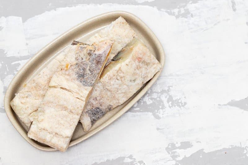 Peixes de bacalhau secos salgados no prato fotos de stock