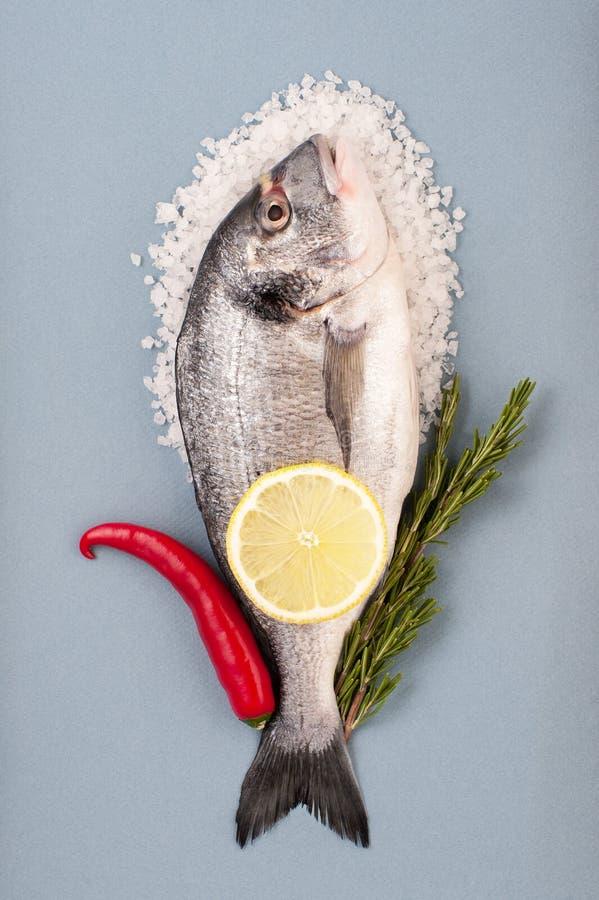 Peixes de Dorado, grande sal do mar, pimentão, limão e alecrins em um ligh fotos de stock