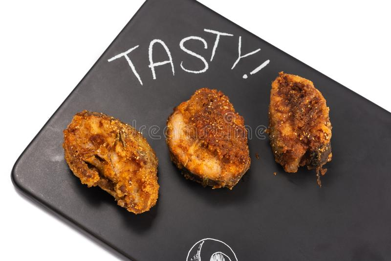 Peixes de Fried Hake na placa preta da bandeja foto de stock royalty free