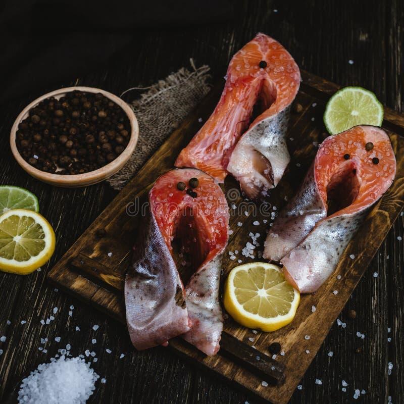 Peixes de mar cortados frescos com especiarias e fatias de limão e de cal na tabela de madeira rústica imagem de stock