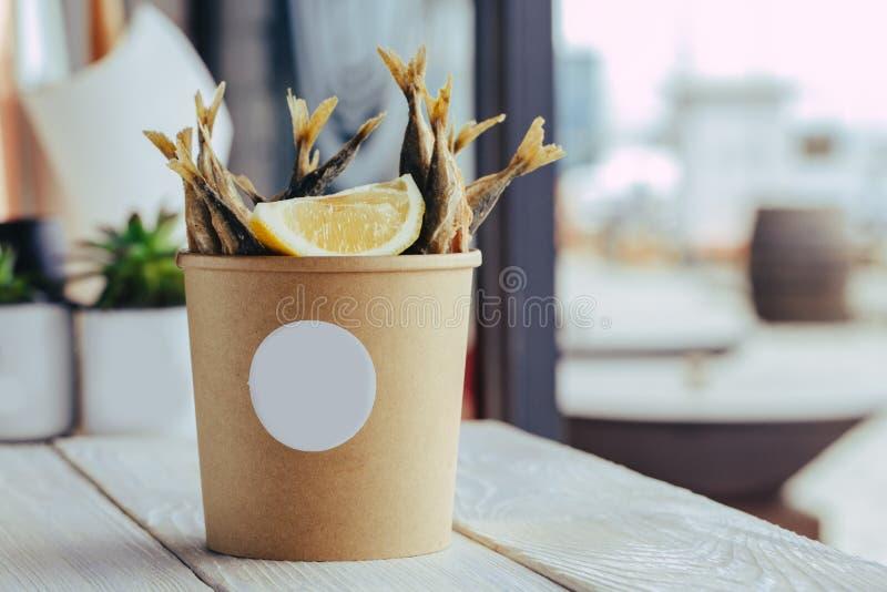 Peixes de mar grelhados com alimento da rua das cunhas de limão na caixa no fundo de madeira fotos de stock royalty free