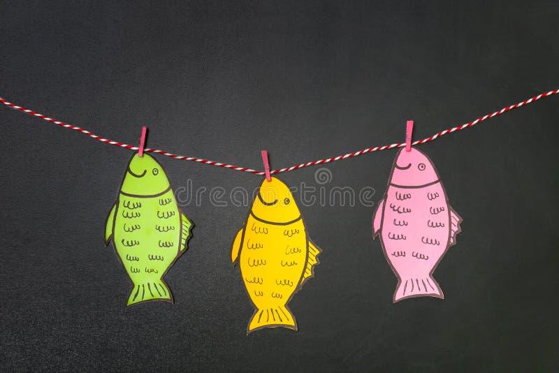 Peixes de papel que penduram na corda perto do quadro fotos de stock royalty free