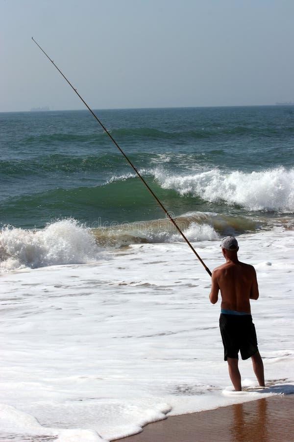 Peixes de travamento do pescador no mar fotografia de stock