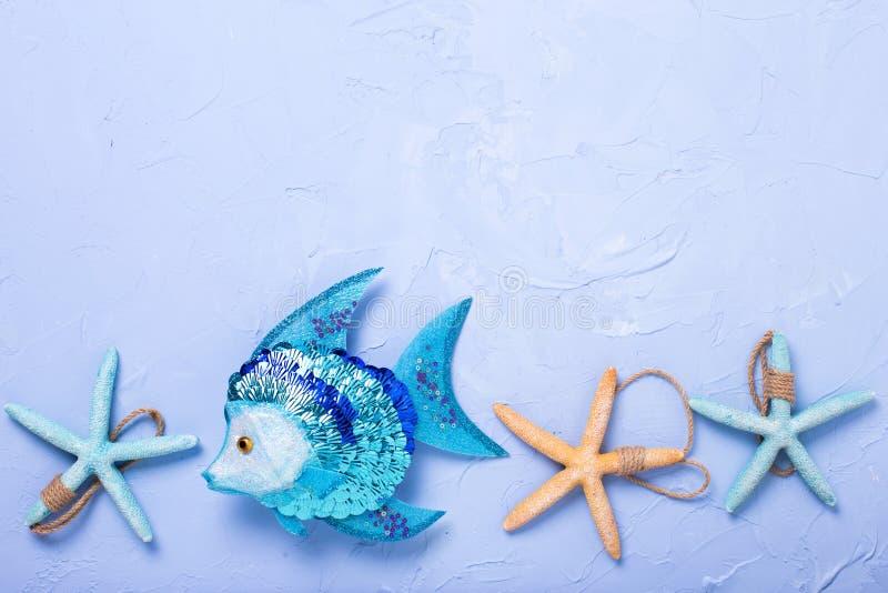 Peixes decorativos e artigos marinhos no fundo textured azul imagens de stock