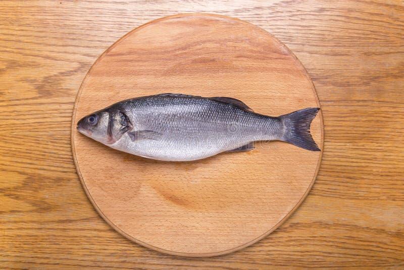 Peixes do badejo em uma opinião superior de placa de madeira fotografia de stock