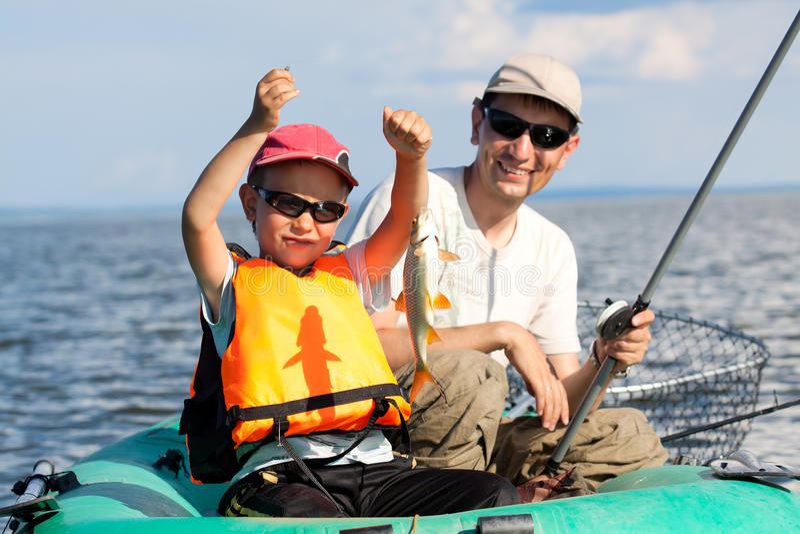 Peixes do pai e do filho em um barco fotografia de stock