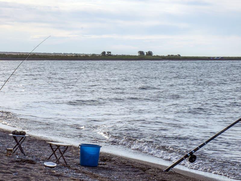 Peixes do pescador cedo na manhã na costa Vara de pesca e gerencio acampar fotos de stock