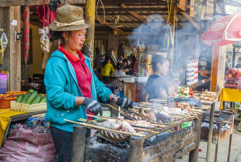 Peixes e carne de cozimento na grelha da mulher fotos de stock