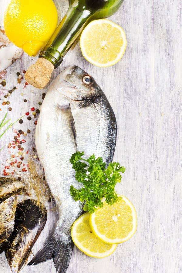 Peixes e mexilhões crus frescos do dorado com a garrafa do vinho branco fotos de stock