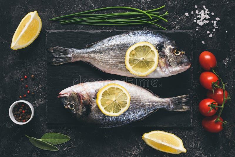 Peixes frescos com especiarias, vegetais e ervas no fundo da ardósia pronto para cozinhar imagem de stock