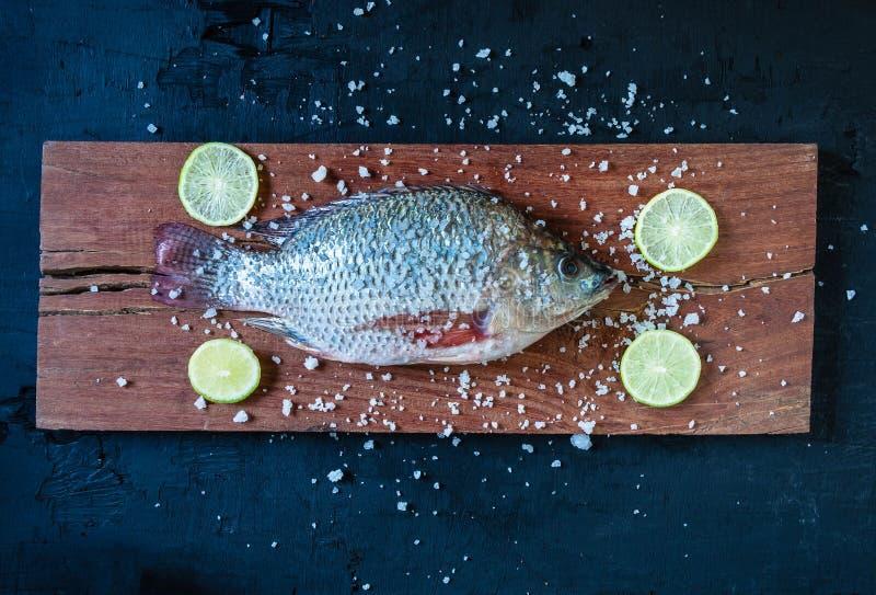 Peixes frescos do tilapia na placa de desbastamento de madeira imagem de stock