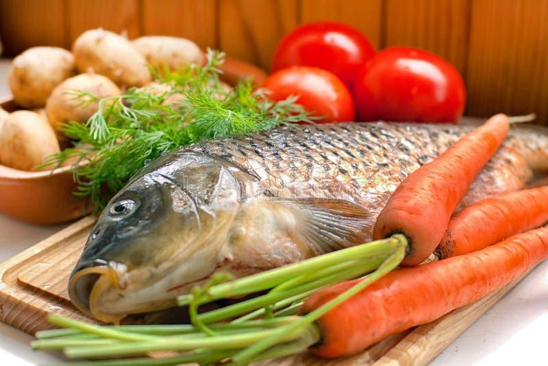 Peixes frescos em uma placa de madeira com vegetais imagens de stock