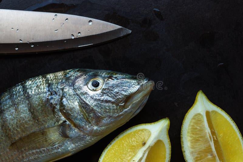 Peixes frescos em uma tabela de pedra preta Fatias de limão suculento e de um l imagem de stock