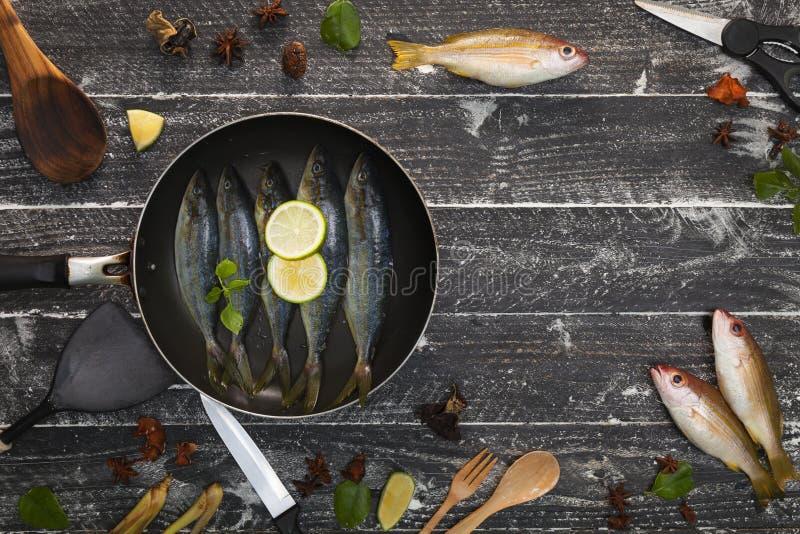 Peixes frescos na frigideira preta no fundo do preto escuro, wi dos peixes imagens de stock royalty free