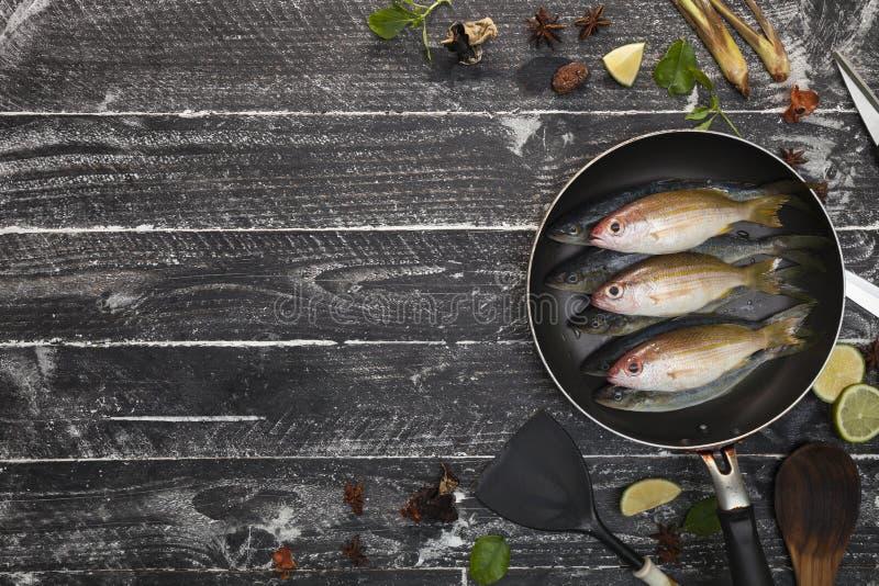 Peixes frescos na frigideira preta no fundo do preto escuro, wi dos peixes fotografia de stock