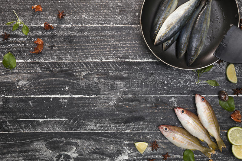 Peixes frescos na frigideira preta no fundo do preto escuro, wi dos peixes foto de stock